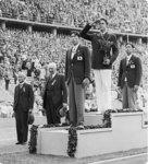 表彰式で国旗掲揚を見つける西田選手、メドウス選手、大江選手